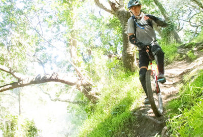 Mountain unicyclist riding a steep chute over a root