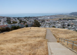View from top of hill at McClaren Park in San Francisco. The hill in the foreground is grassy; a San Francisco neighborhood is in the background. A unicycle is climbing the trail.