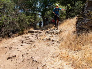 Mountain unicyclist near the top of rocky, dry section of trail.