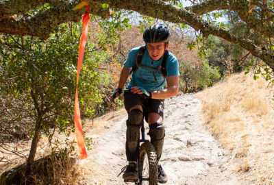 Mountain unicyclist on rocky trail ducking under an overhanging tree limb